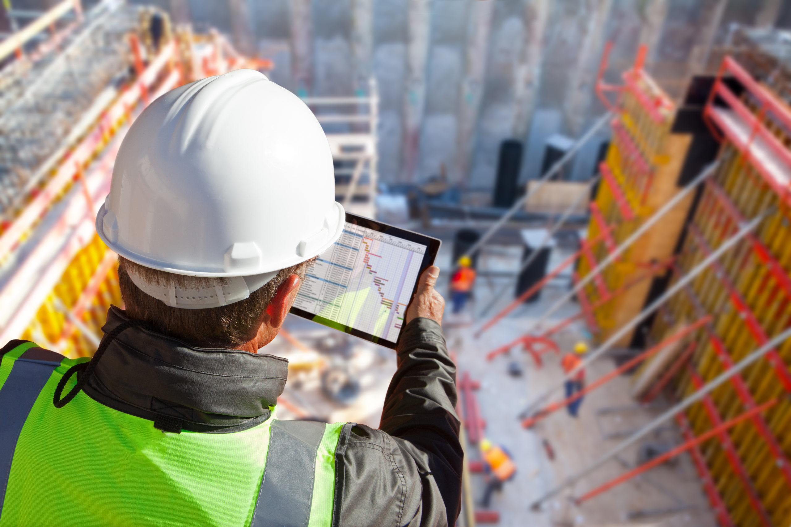 Construction worker looking over construction site while holding a tablet